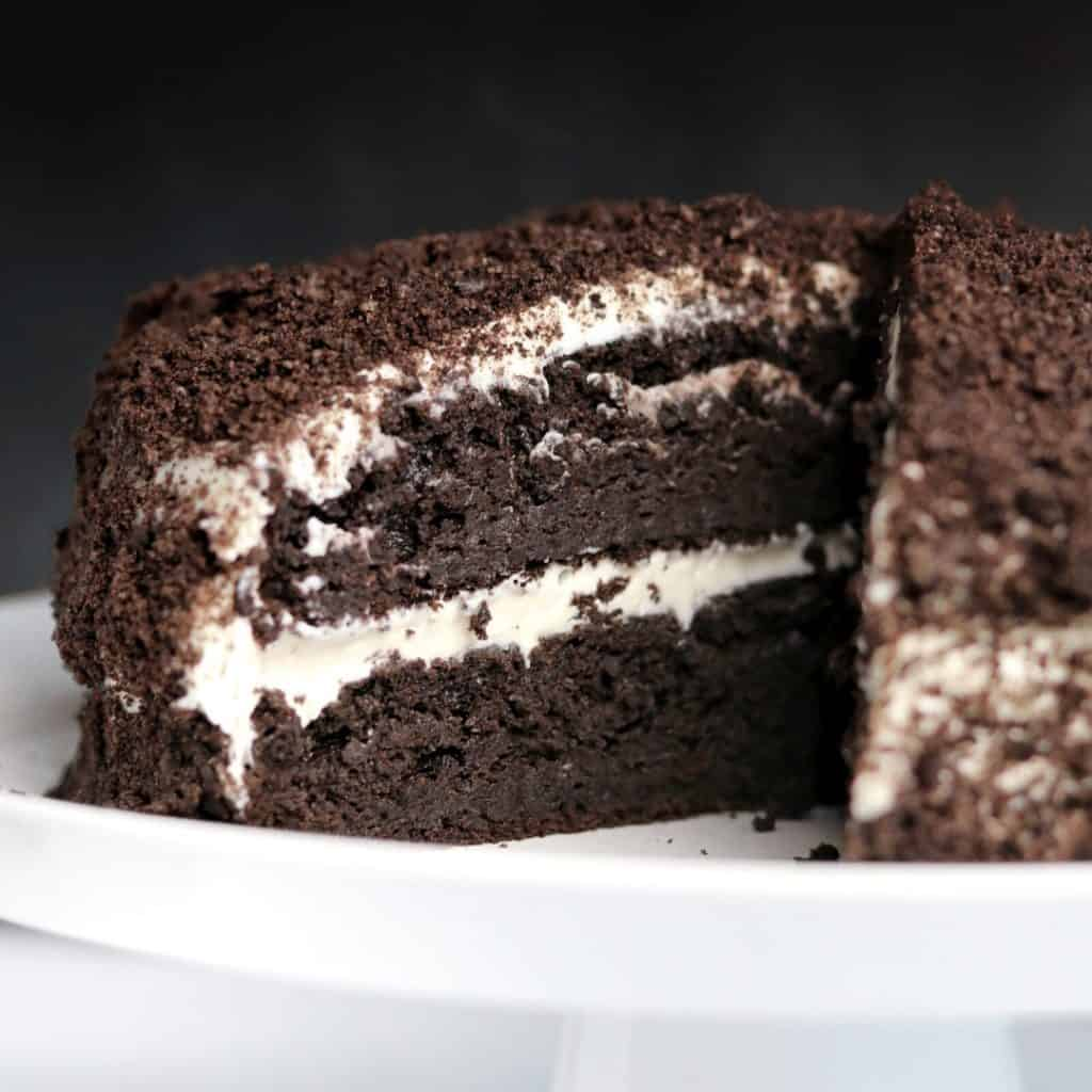oreo protein cake with a slice cut out sitting on a white serving dish