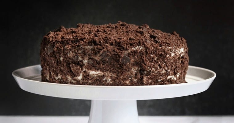 chocolate cake with cream frosting and crushed oreos on a white cake serving dish