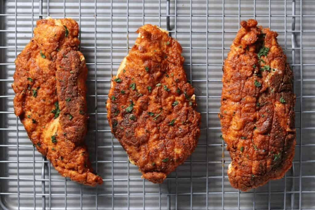 pan fried buttermilk chicken breasts on a wire cooling rack