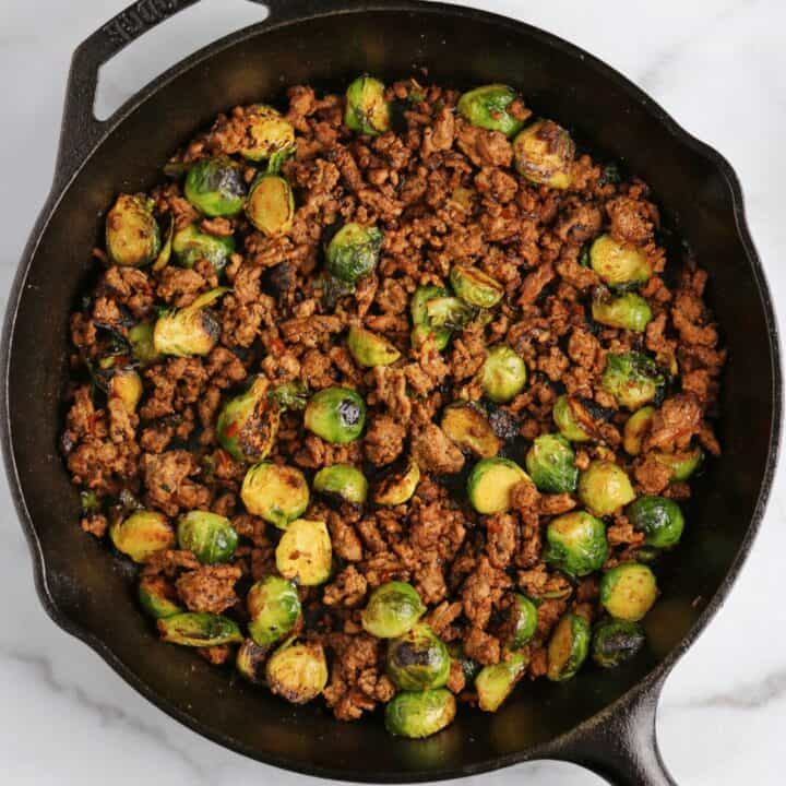 sweet chili ground beef and brussels sprouts in a cast iron skillet