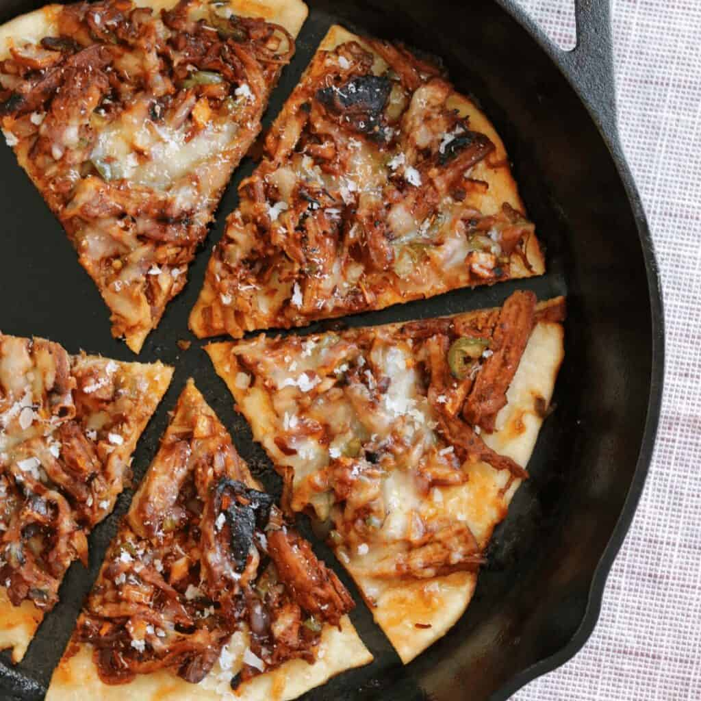 slices of pulled pork pizza in a cast iron skillet