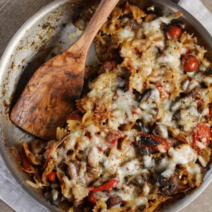 Italian sausage pasta bake in a stainless steel skillet with wooden spatula