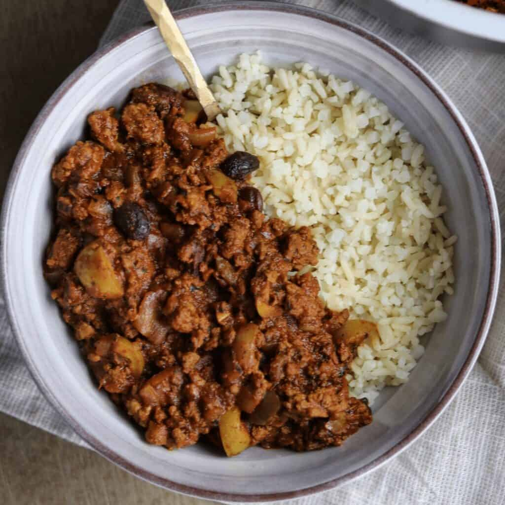picadillo in a bowl with whole grain and cauliflower rice
