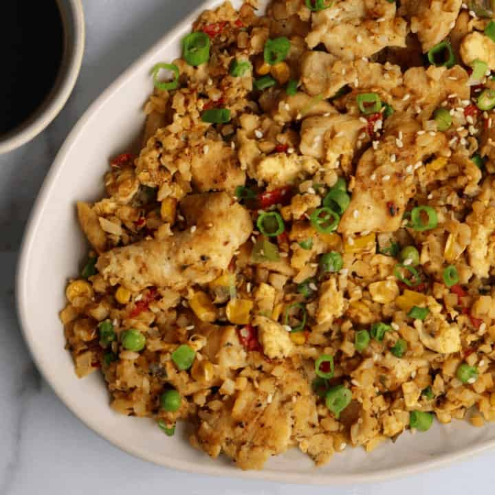 spicy chicken fried cauliflower rice stir fry on a white plate