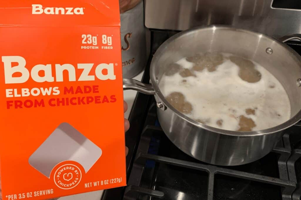 a box of Banza elbows cooking in a pot of boiling salted water