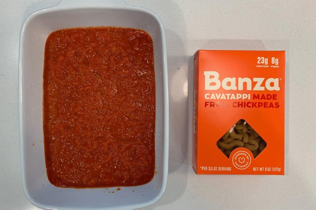 baking dish with marinara next to a box of Banza cavatappi