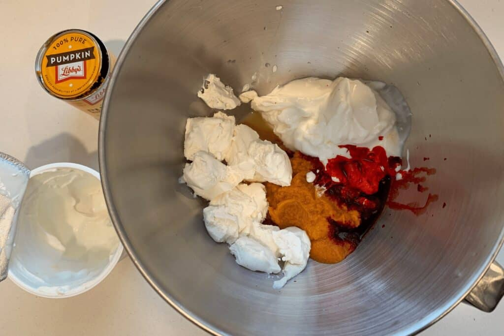 fat free cream cheese, Greek yogurt, canned pumpkin, red food coloring, and white vinegar in a mixing bowl