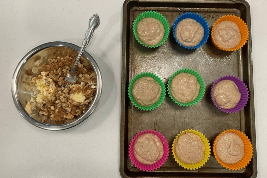 coffee cake muffin batter in silicone molds beside a bowl of walnuts, oats, butter, and brown sugar
