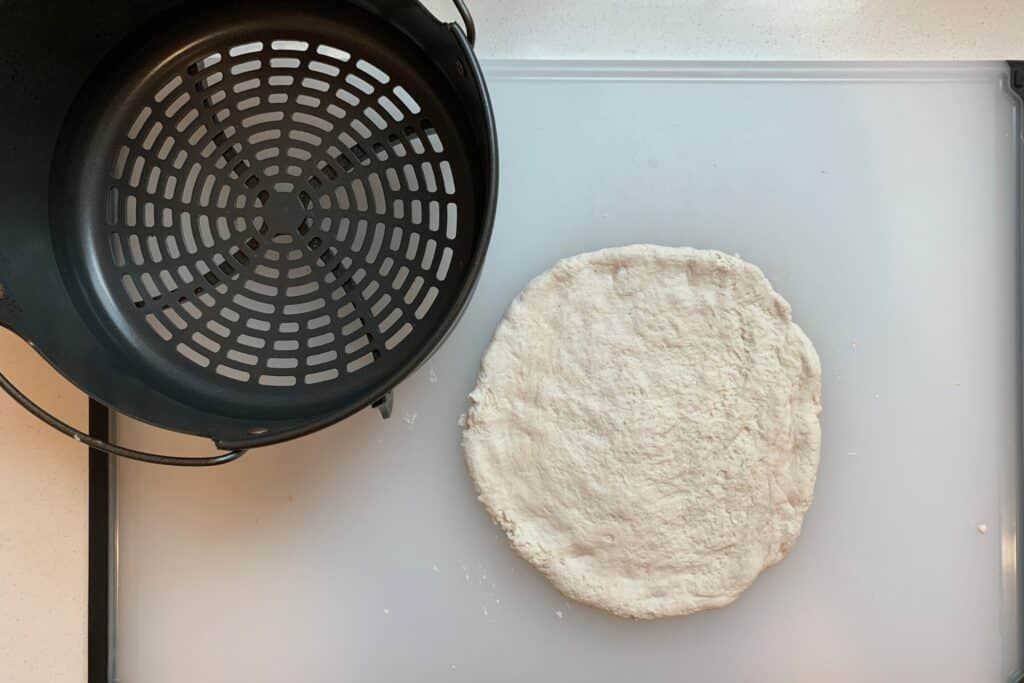 Greek yogurt pizza dough beside Ninja Foodi air fryer basket