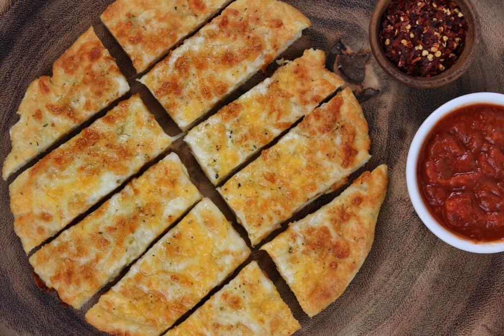 sliced cheese bread with marinara and red pepper flakes