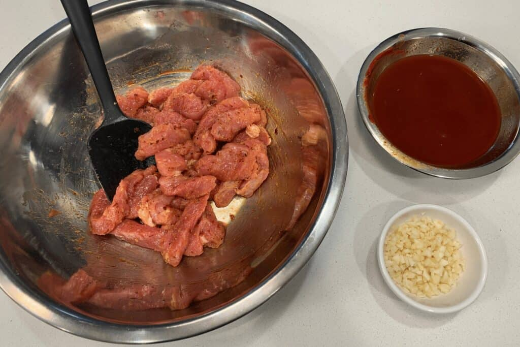 seasoned pork tenderloin strips beside a bowl of sweet and spicy sauce and minced garlic