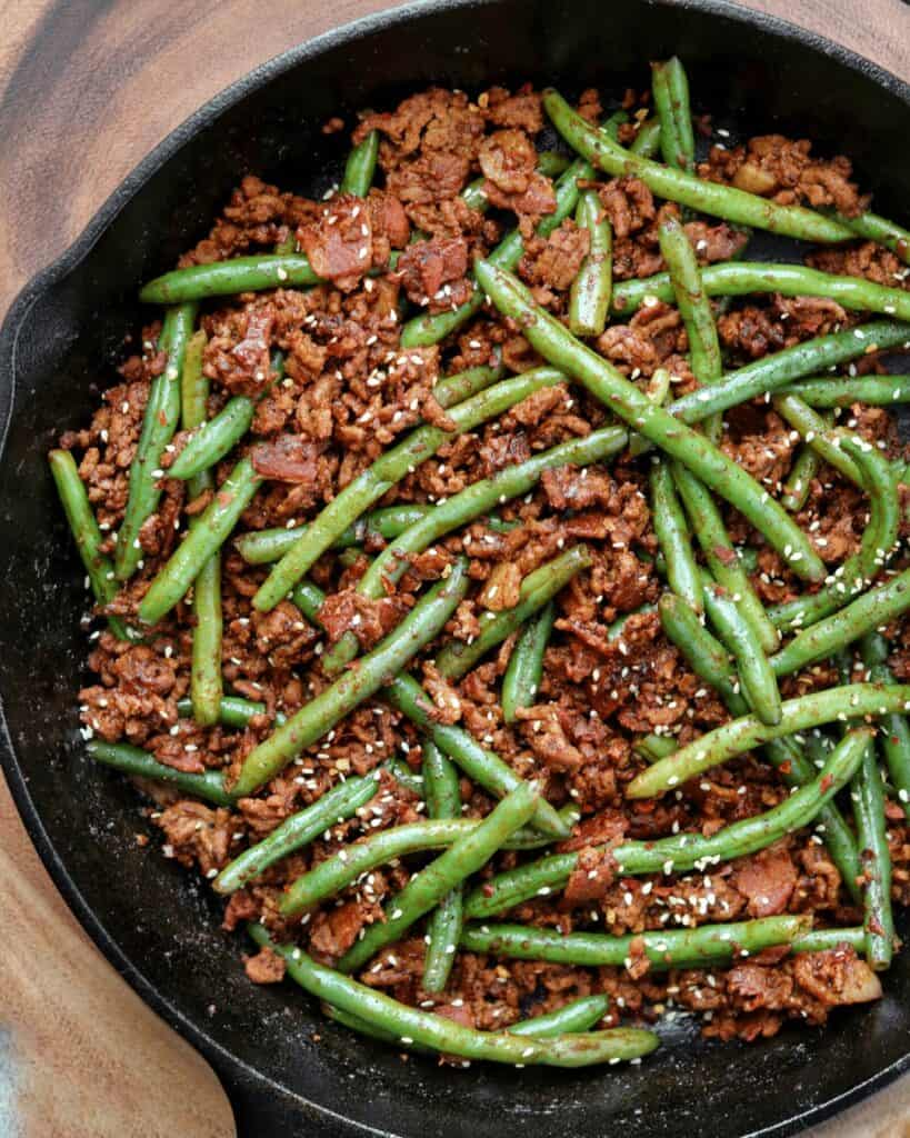 cast iron skillet with ground beef, bacon, and green beans