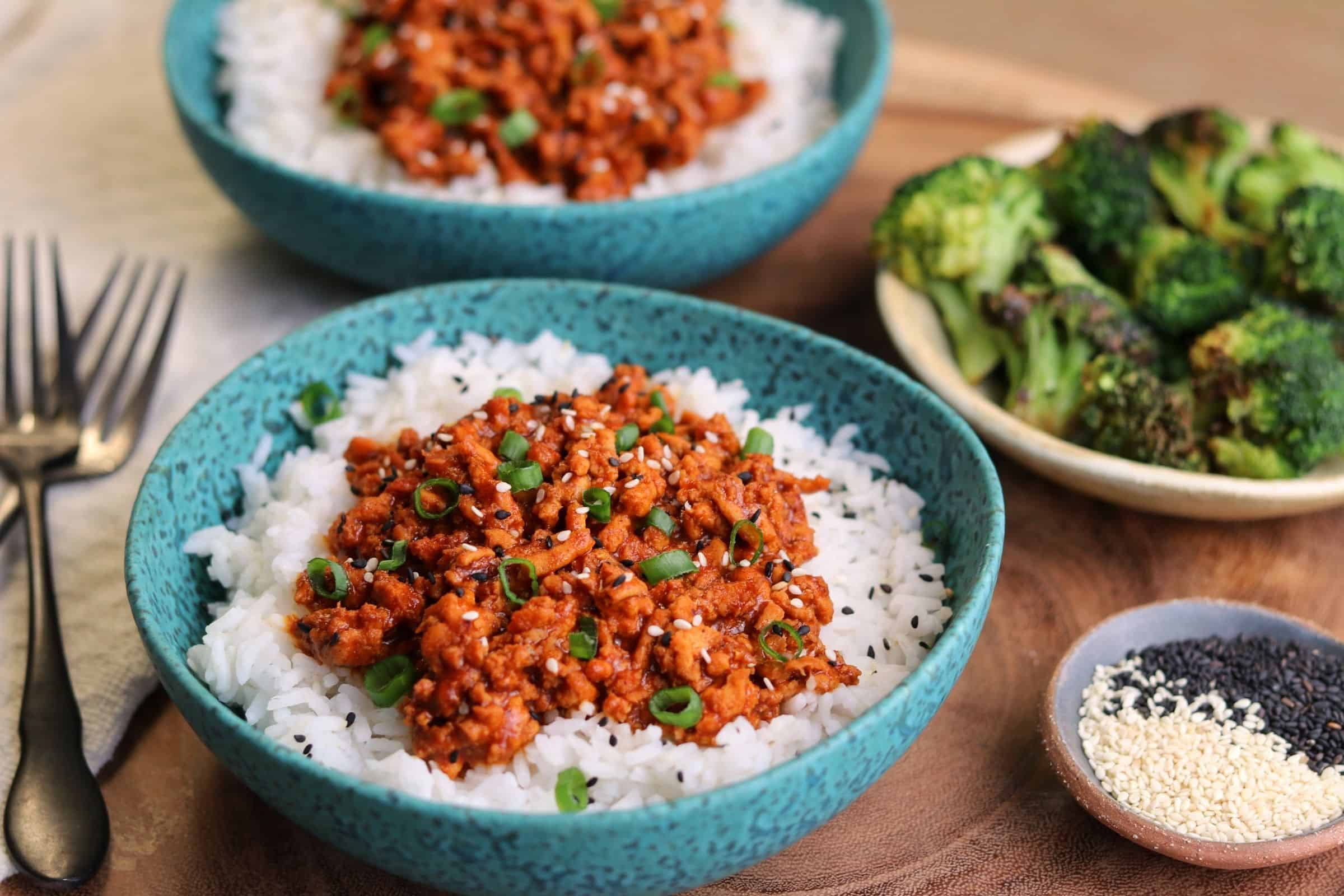 chili coconut ground chicken over rice in a bowl beside air fried broccoli and sesame seeds