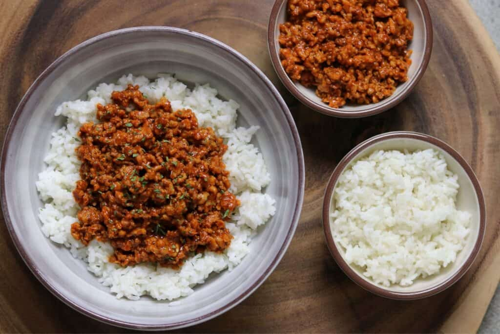 spicy coconut ground chicken in a bowl with rice