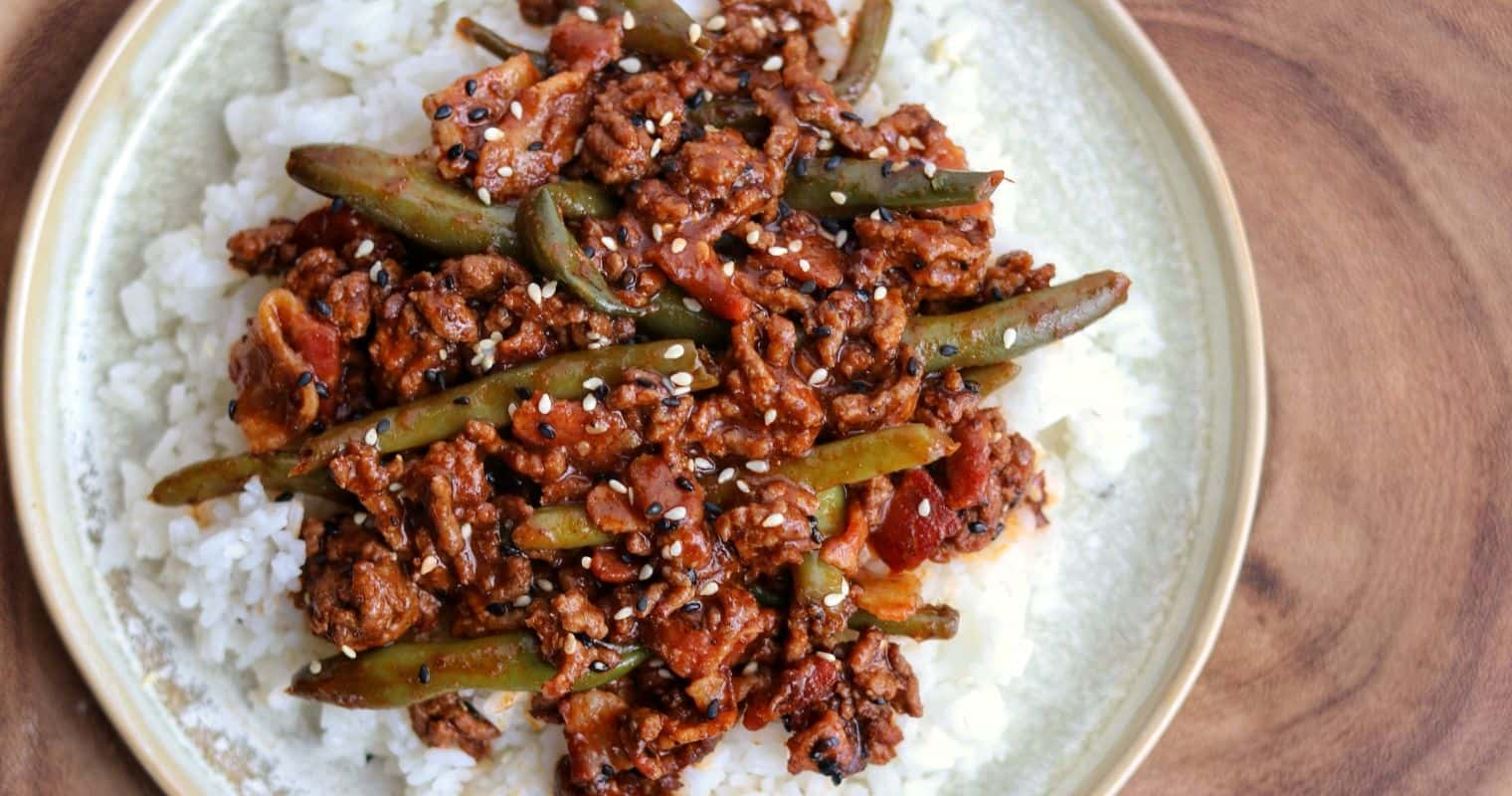 ground beef and green beans on a plate with rice and toasted sesame seeds