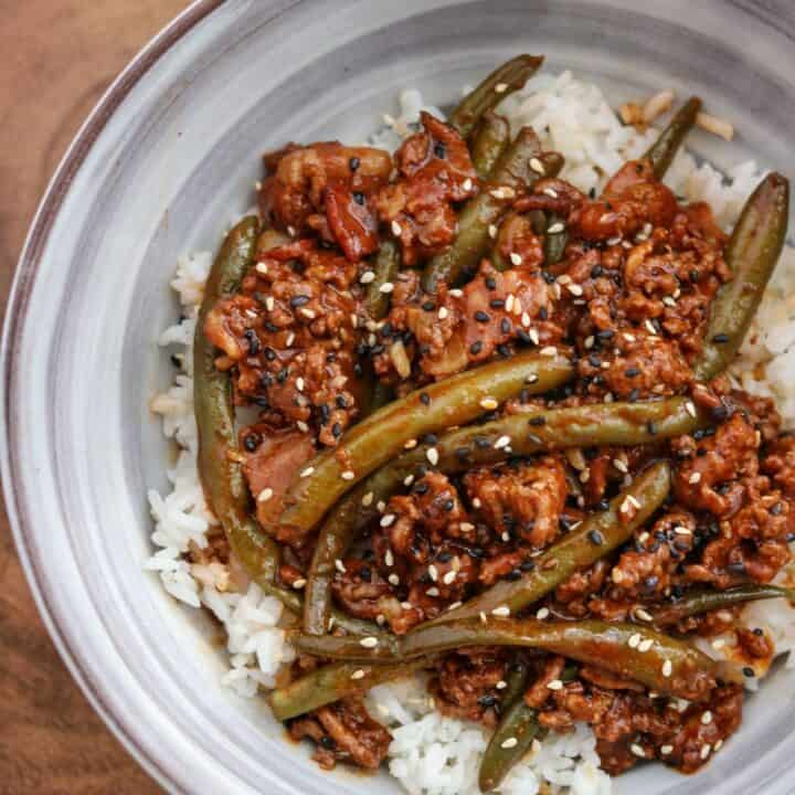 sriracha bbq ground beef in a bowl over rice with toasted sesame seeds and black sesame seeds