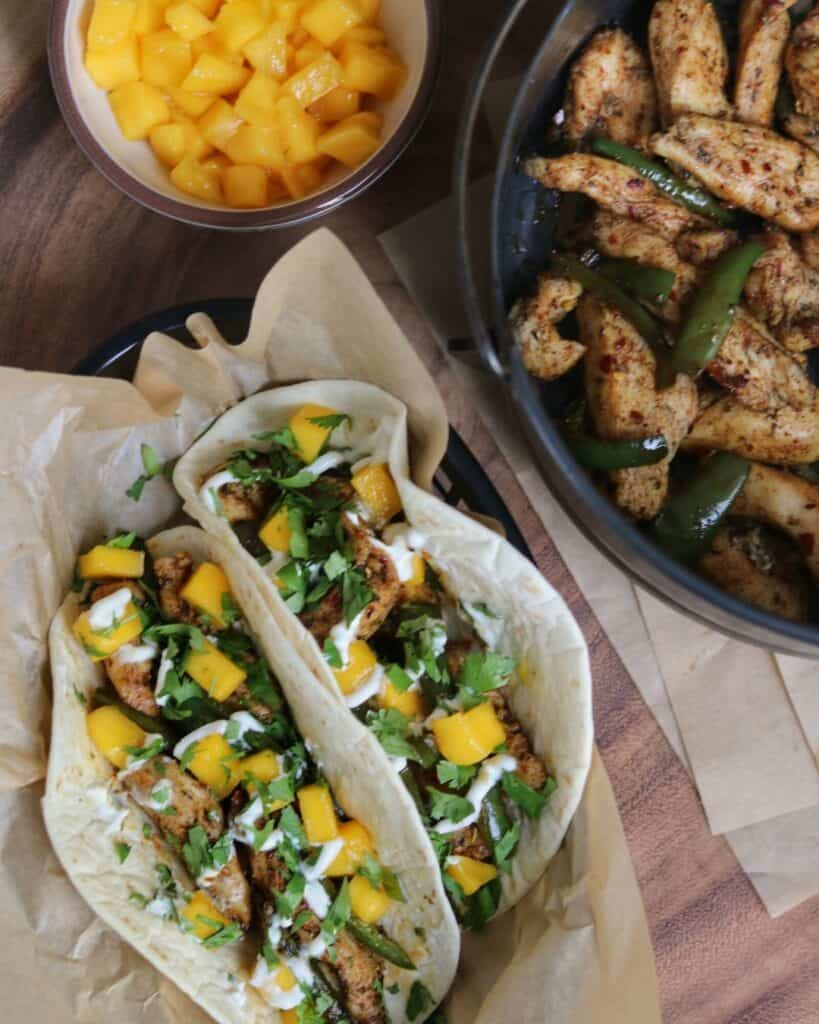 copycat brushfire tacos beside a bowl of diced mango and air fryer basket with jerk chicken and jalapeños