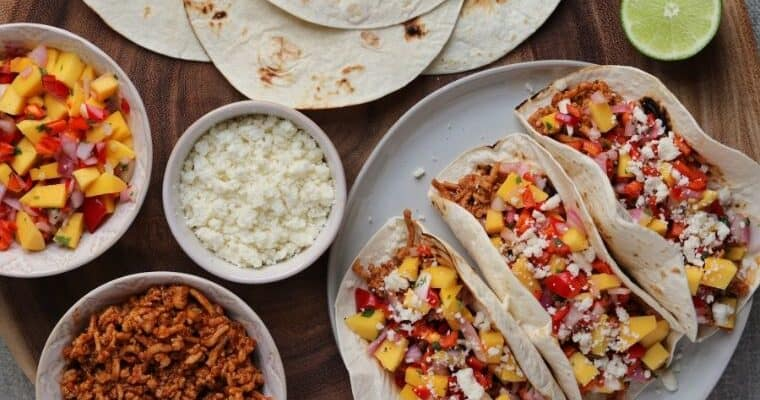 chipotle bbq ground chicken tacos on a plate beside mango salsa and cotija cheese