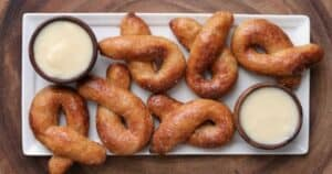 cinnamon bread twists on a white plate with 2 bowls of buttercream dipping sauce