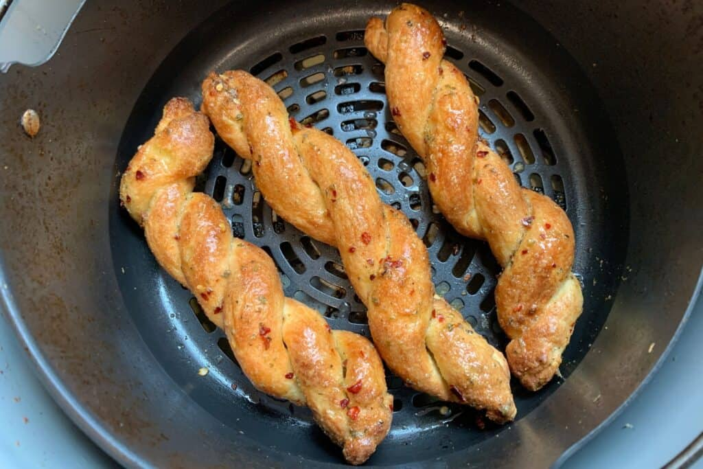cooked bread twists in the Ninja Foodi air fryer basket after brushing with the butter sauce