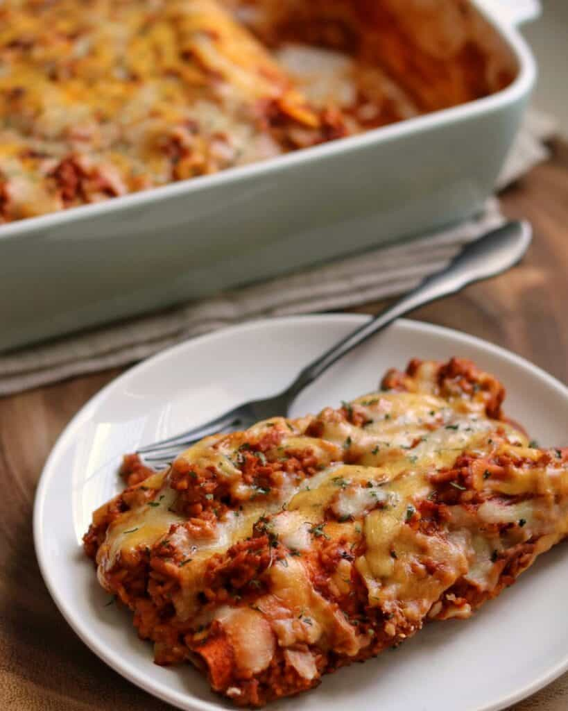 two chicken and rice enchiladas on a plate beside a baking dish