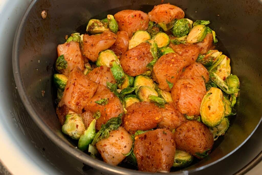 seasoned chicken breast in an air fryer basket with brussels sprouts