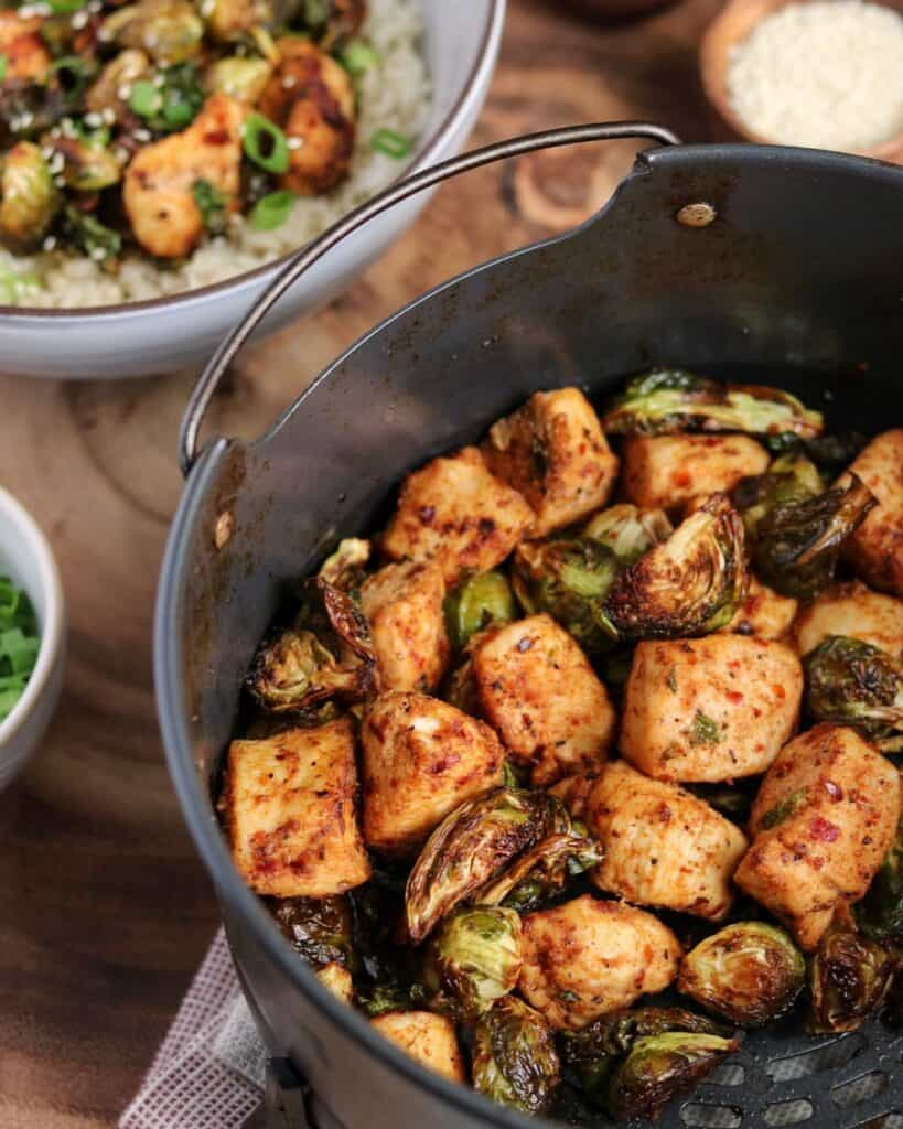 air fried chicken and brussels sprouts in the Ninja Foodi air fryer basket