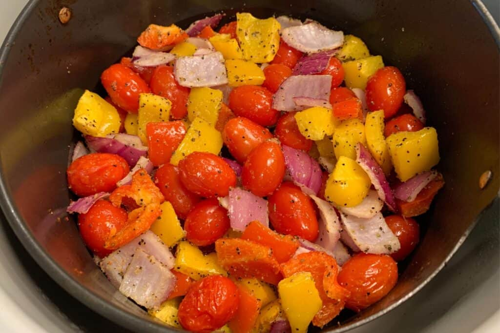 diced red onion, bell pepper, and grape tomatoes in the Ninja Foodi air fryer basket