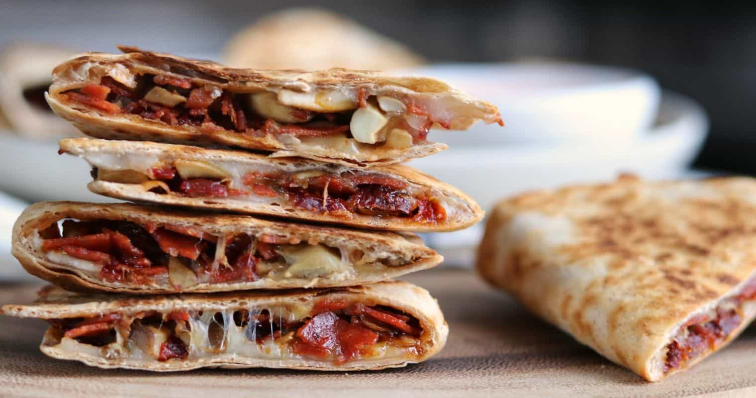 sliced pizza quesadillas on a wooden serving board