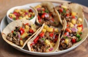 jerk pork tenderloin tacos on a plate with pineapple salsa