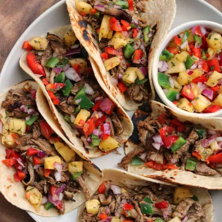jerk pork tenderloin tacos on a plate with a bowl of pineapple salsa