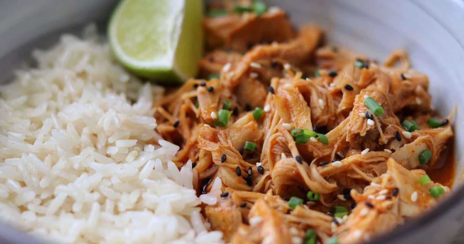 spicy coconut pulled chicken thighs in a bowl with jasmine rice and a lime wedge