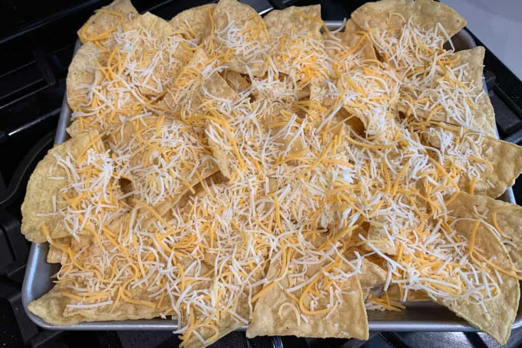 tortilla chips with shredded cheese on a baking sheet