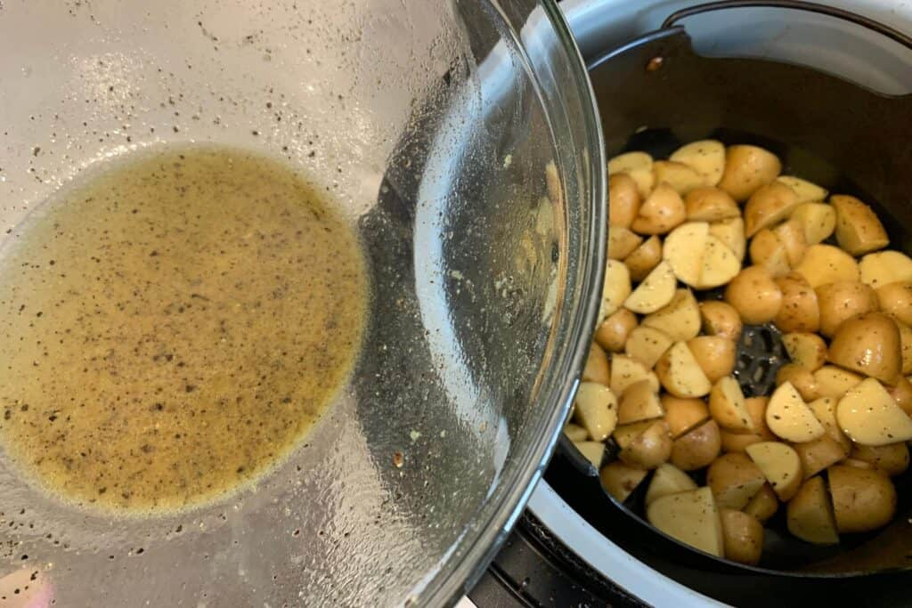 Greek potatoes in the air fryer basket with remaining olive oil and lemon juice in the mixing bowl