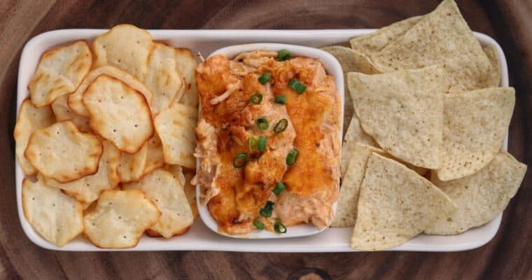 buffalo chicken dip in a bowl with chips and crackers