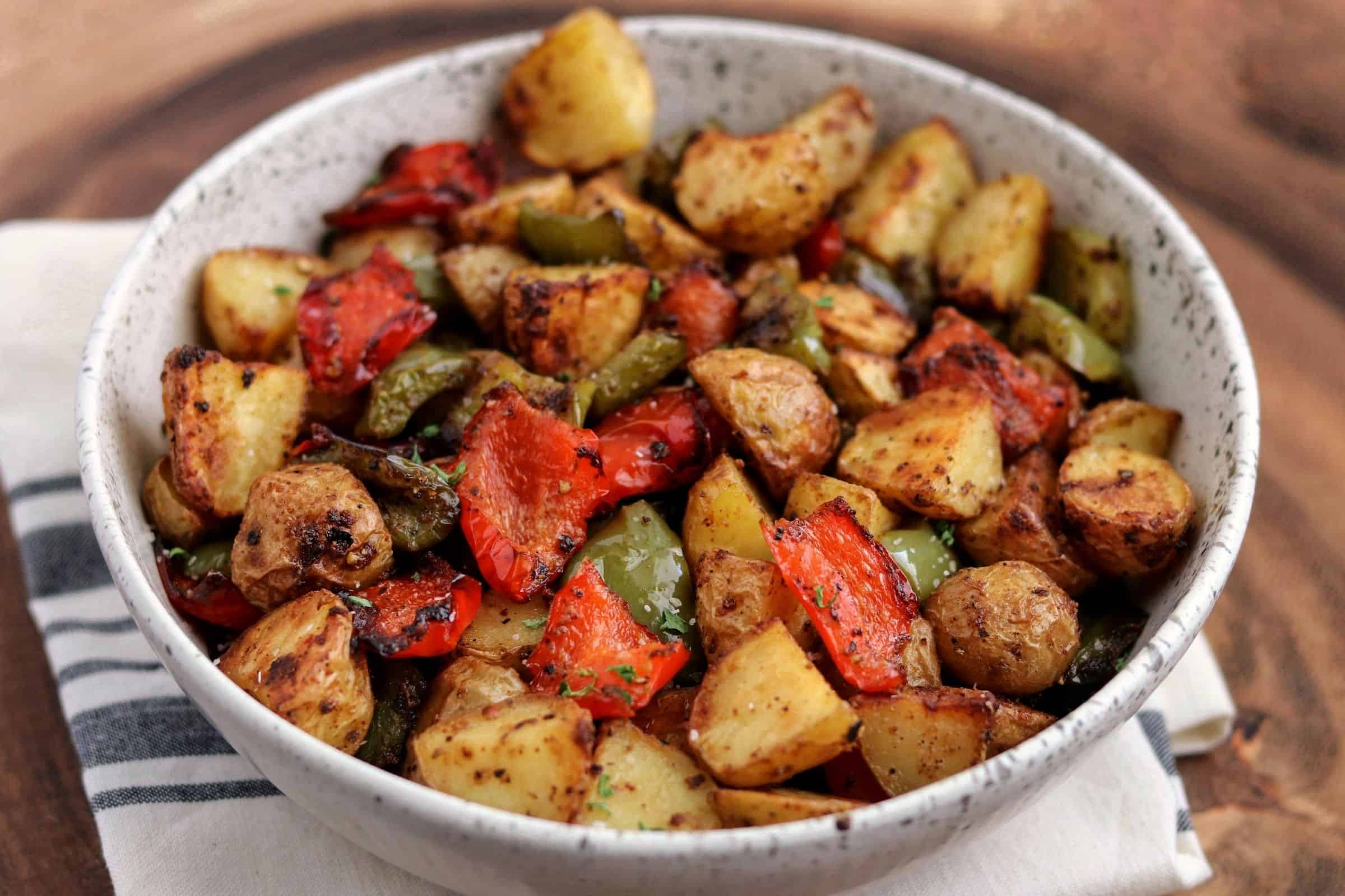 air fried breakfast potatoes with bell pepper in a white bowl