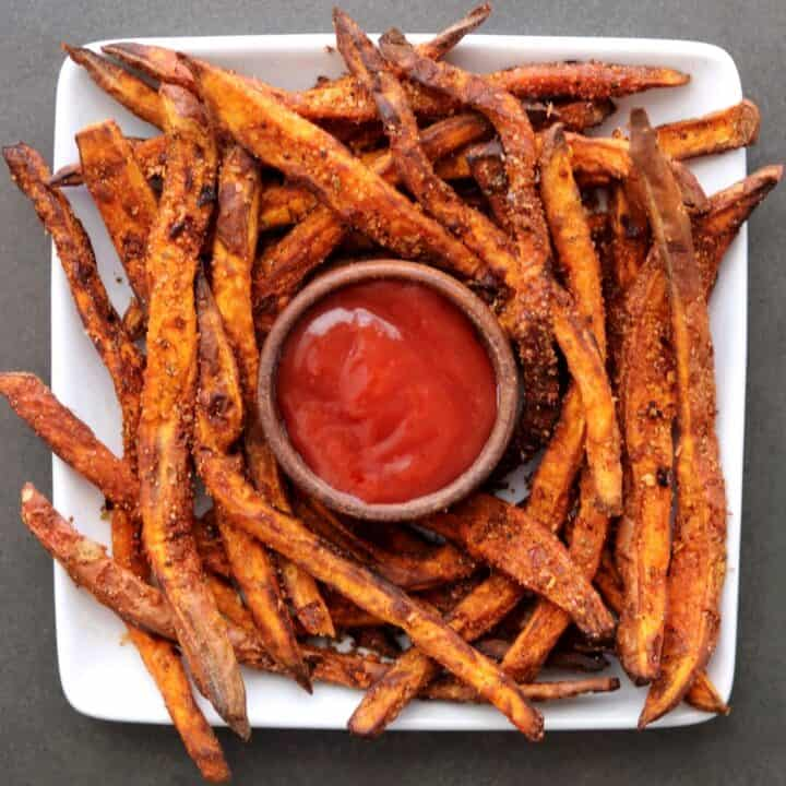sweet potato fries on a white plate with ketchup