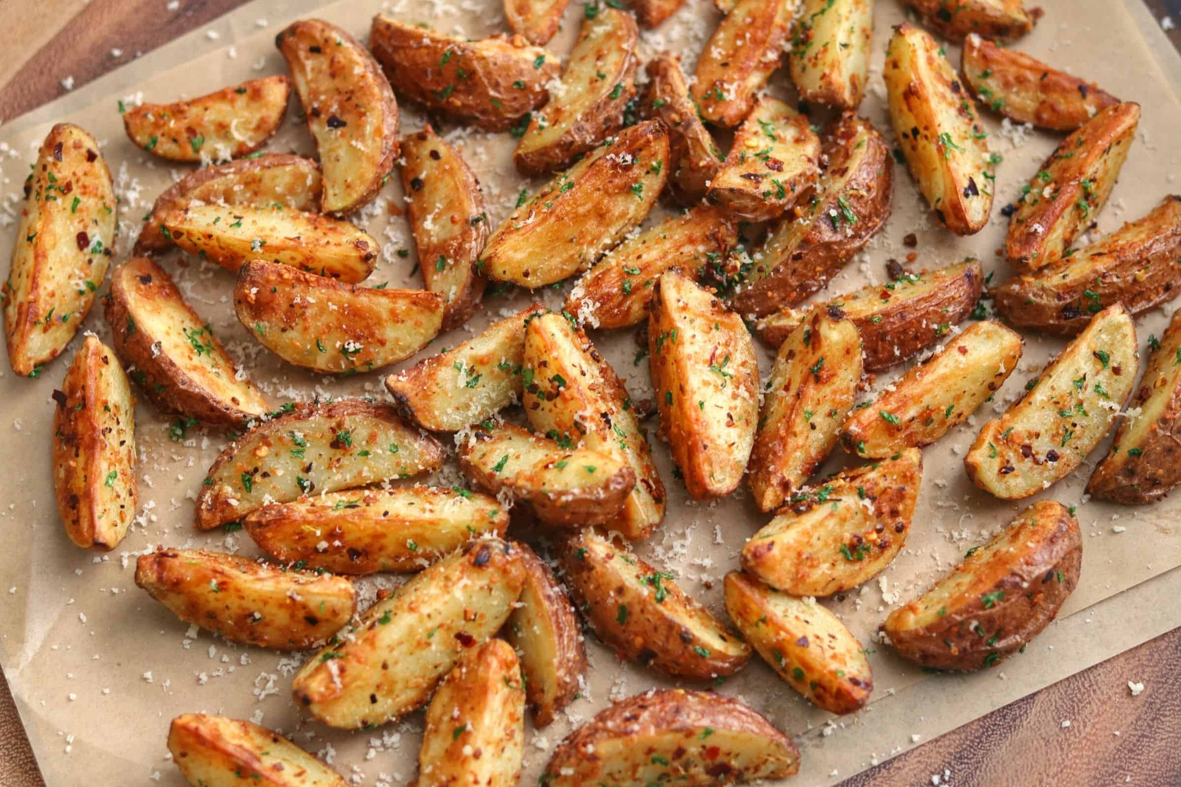 garlic parmesan air fryer red potatoes on parchment paper with grated parmesan and parsley flakes