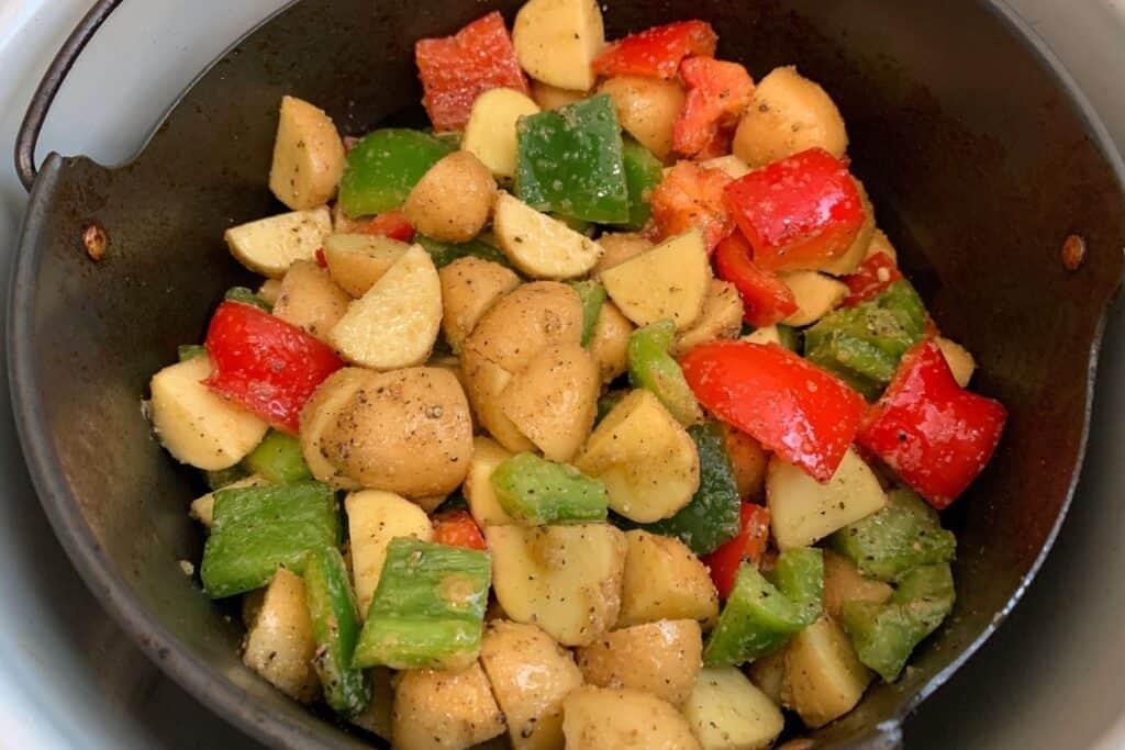 seasoned breakfast potatoes and bell pepper in the ninja foodi air fryer basket
