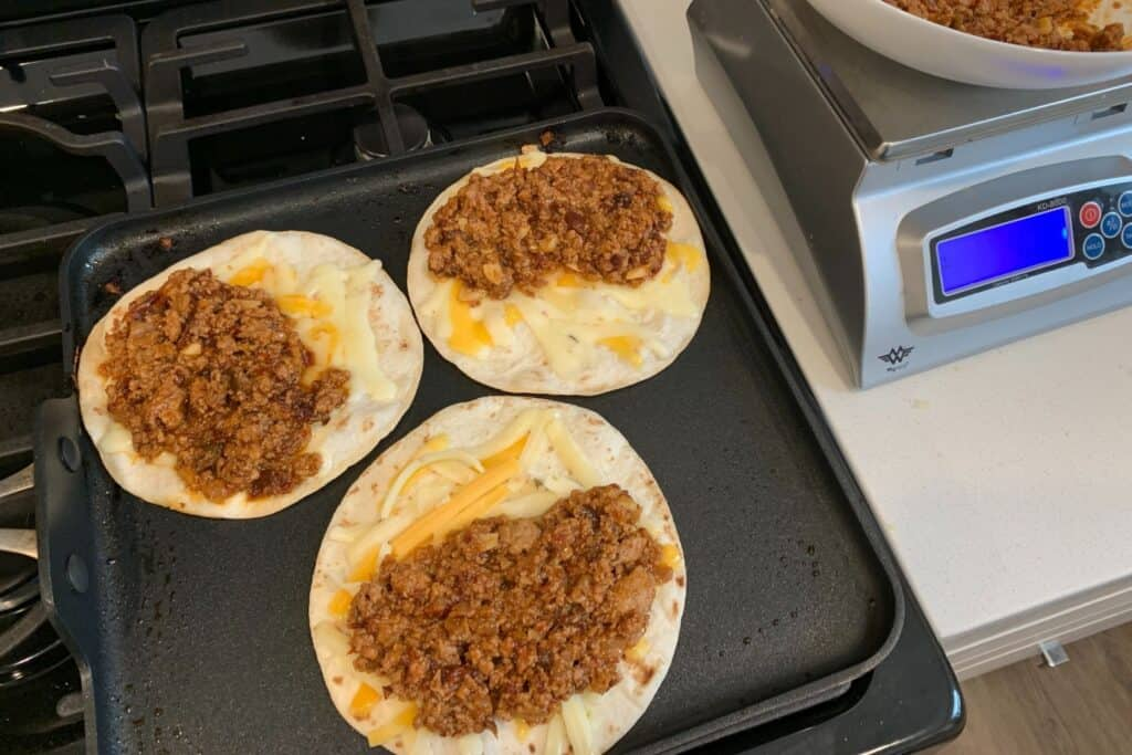 3 flour tortillas with cheese and taco meat on a griddle