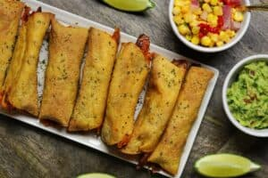 chicken taquitos on a plate with corn salsa, guacamole, and lime wedges
