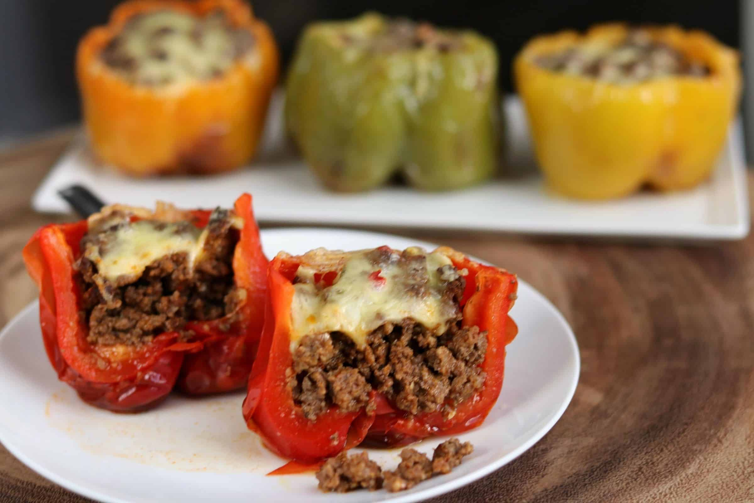 stuffed pepper cut in half on a white plate with 3 stuffed peppers in the background