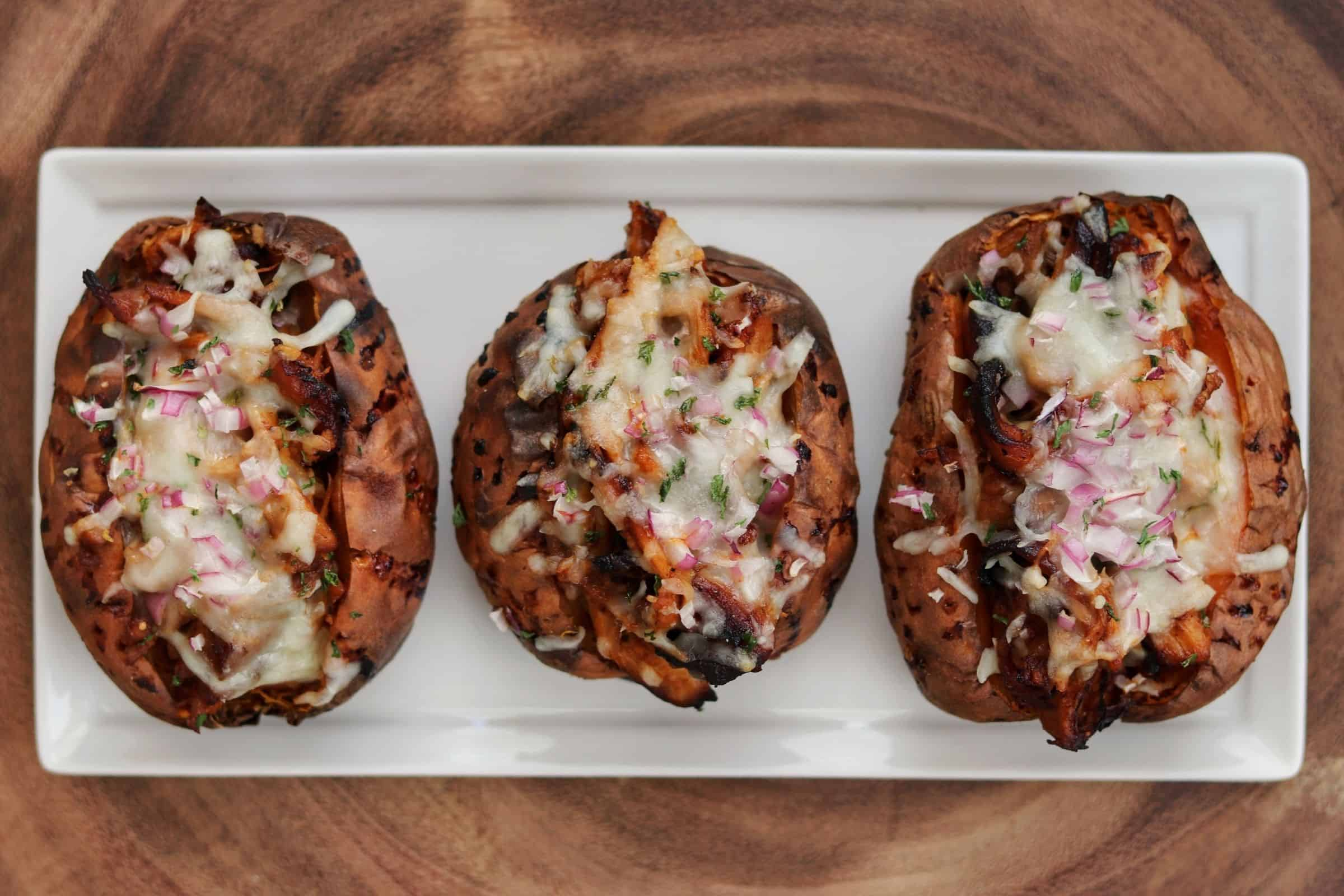 3 bbq chicken stuffed sweet potatoes on a plate