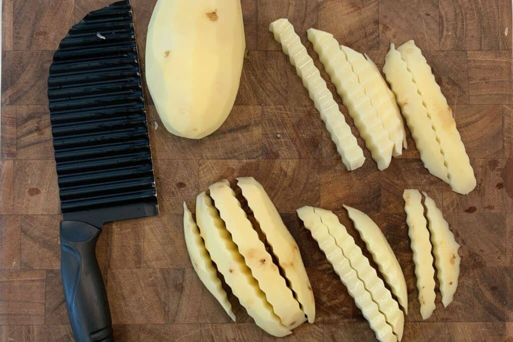peeled potatoes and a crinkle cut fries cutter