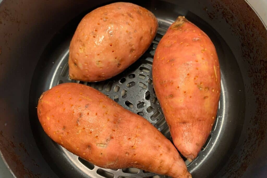 sweet potatoes with holes poked in them inside an air fryer basket