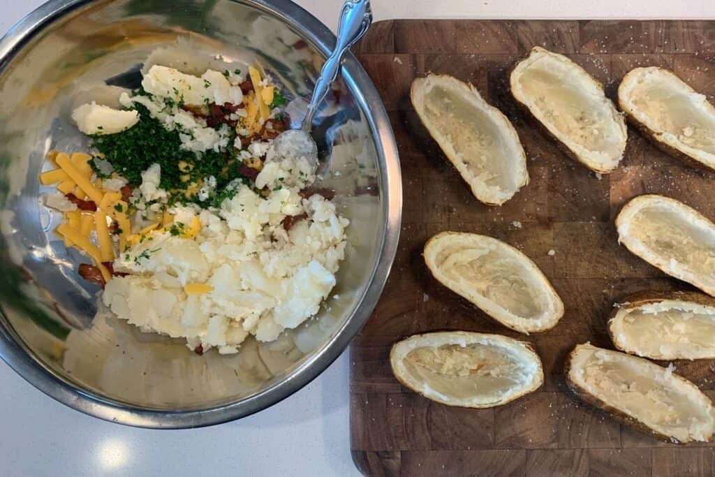 baked potatoes scooped into a bowl with butter, cheddar, cooked bacon, and parsley
