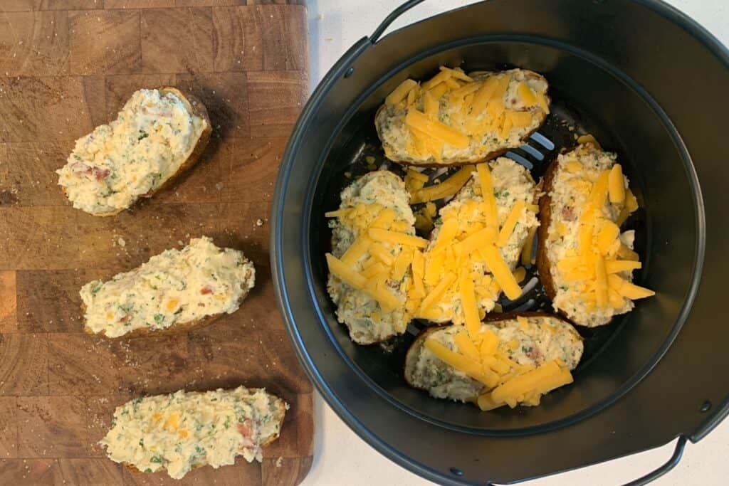 filled potatoes back in the air fryer topped with cheddar