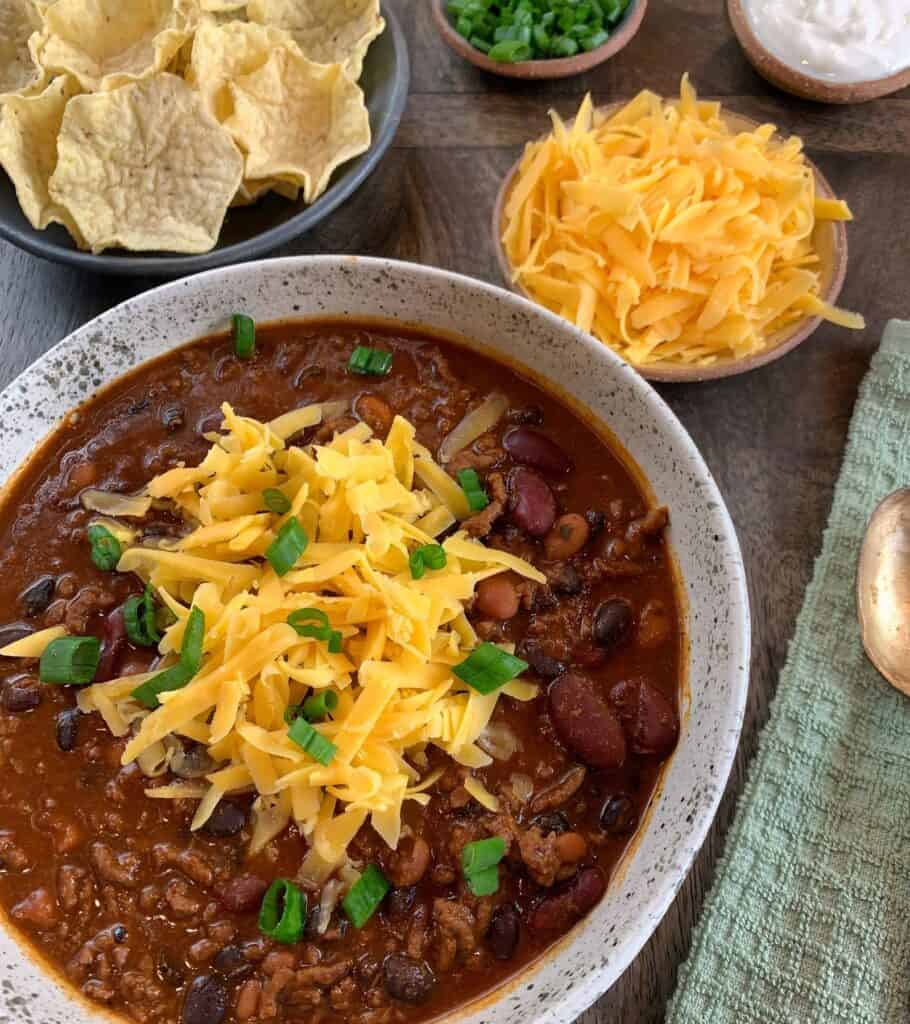 high protein chili in a bowl with shredded cheddar cheese, scallions, and baked tortilla scoops