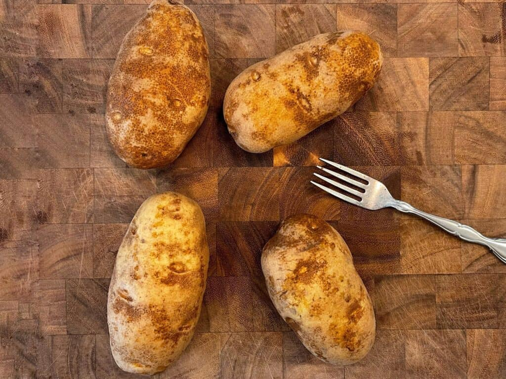 4 russet potatoes with holes poked in them