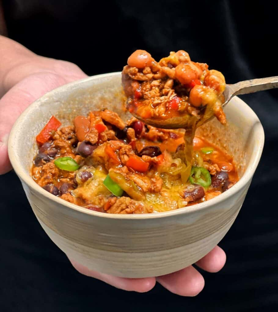 holding a bowl of turkey chili with melted cheddar